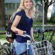 Stock Photo: Female student standing with her bike
