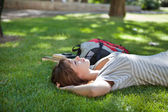 Girl lying on grass at campus lawn — Stock Photo