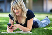 Happy young girl using cell phone — Stock Photo