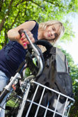 Cute female student standing with her bike — Stock Photo