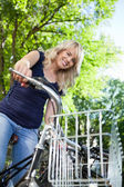 Beautiful female student standing with her bike — Stock Photo