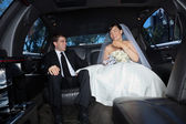 Newly wed couple in limousine — Stock Photo