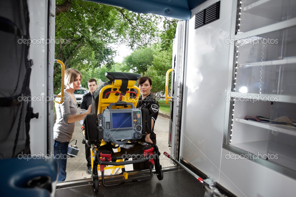 Emergency team loading patient in ambulance, caregiver at side — Stock Photo #7086351