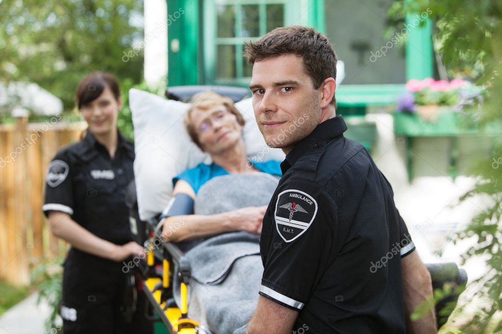 Serious ambulance worker with patient on stretcher — Stock Photo #7087545
