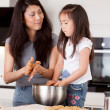 Stock Photo: Mother with Young Daughter Baking Cookies