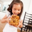 Young Girl Eating Stack of Cookies - Stock Photo