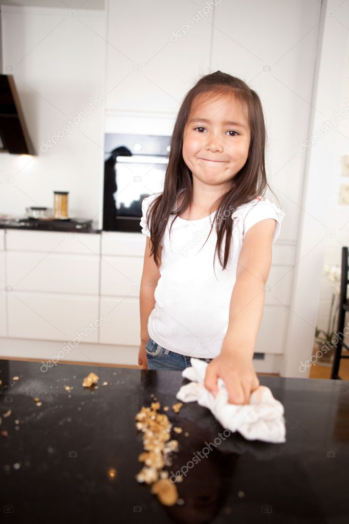 Young smiling cute girl wiping the counter after making cookies  Stock Photo #7334315