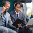 Businessmen using electronic gadgets - Stock Photo