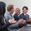 Professionals applauding during a business meeting - Stock Photo