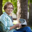 Woman reading newspaper in park — Stock Photo