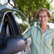 Senior woman standing near car - Stock Photo