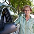 Stock Photo: Senior womstanding near car