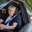 Old woman driving car - Stock Photo
