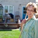 Senior Woman holding gardening tool — Stock Photo