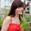 Woman smelling flower - Stockfoto