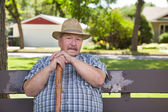 Senior man sitting on park bench — Stock Photo
