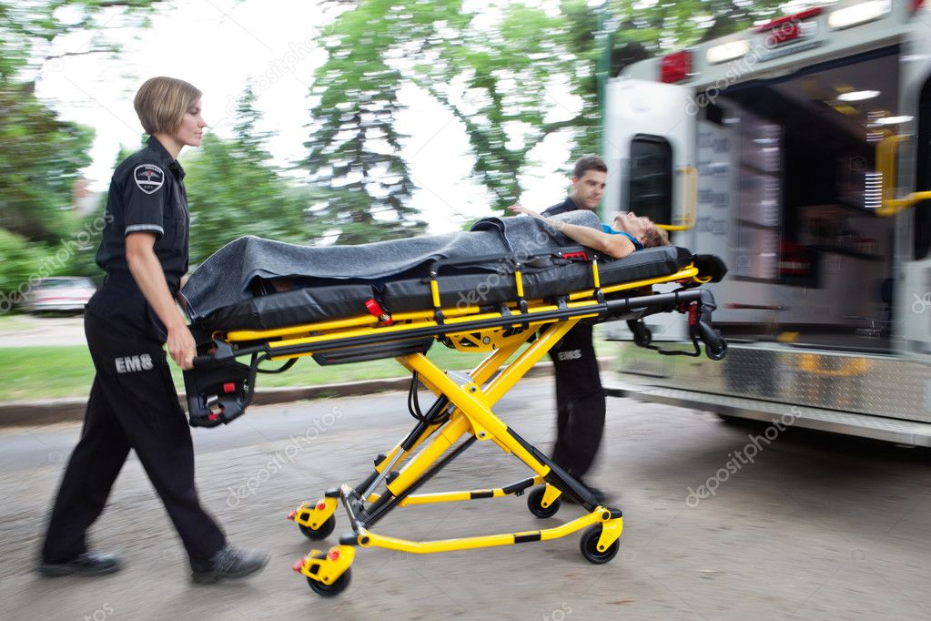 Man and woman ambulance team rushing a senior woman into the vehicle — Stock Photo #7390451