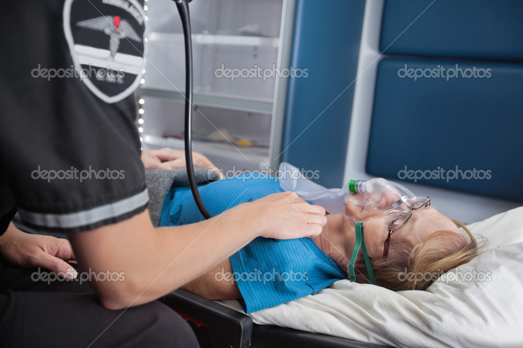 EMT worker listening to pulse of senior woman patient in ambulance  Stock Photo #7391496