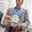 Businessman carrying takeaway cups - Stock Photo