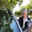 Stock Photo: Senior womStanding by Car