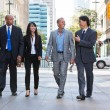 Business walking together on street - Stock Photo