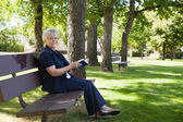 Woman reading book in a park — Stock Photo