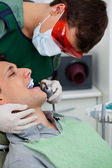 Dentist working on tooth at dental clinic — Stock Photo
