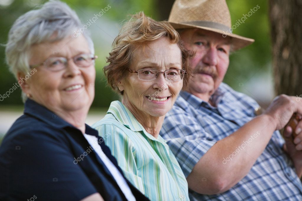 Portrait of senior friends sitting together in park — Stock Photo #7404958