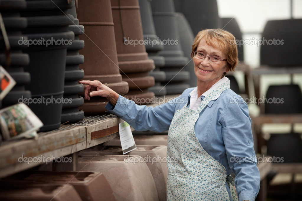 Portrait of a senior woman standing by pots in garden center  Stock Photo #7410925