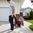 Father Pulling Son Sitting in Wagon - Stock Photo