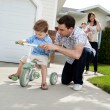 Father Teaching Son To Ride Tricycle - Stockfoto