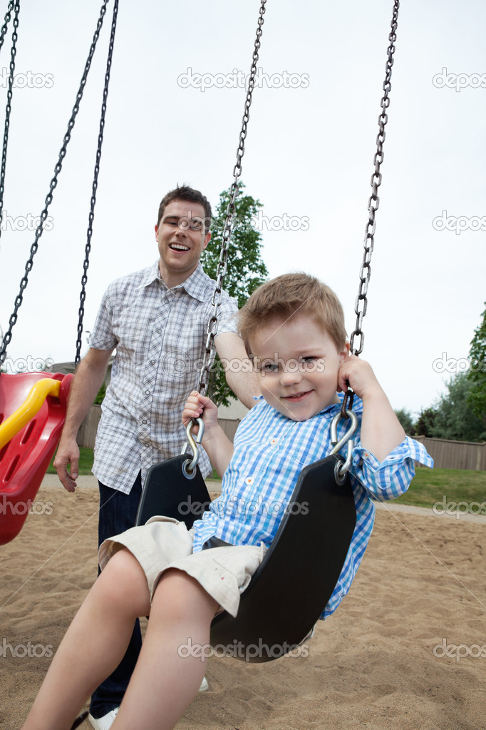 Happy father pushing his son on a swing — Stock Photo #7677197