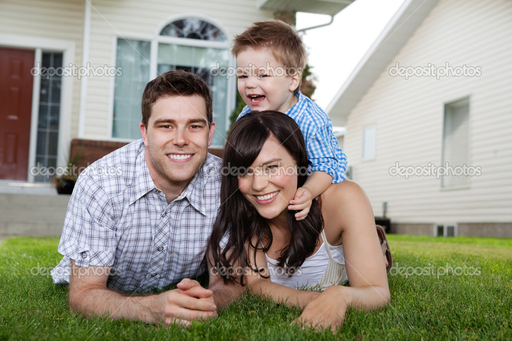 Portrait of cheerful family lying down on grass in front of house — Stok fotoğraf #7677264