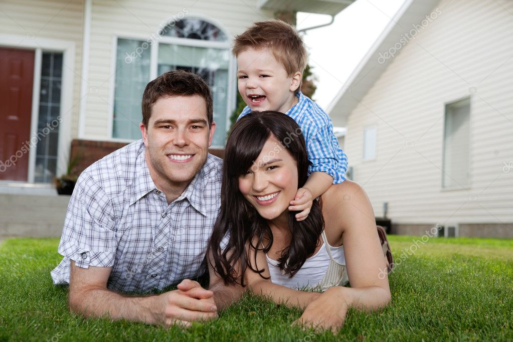 Portrait of cheerful family lying down on grass in front of house — Stockfoto #7677264