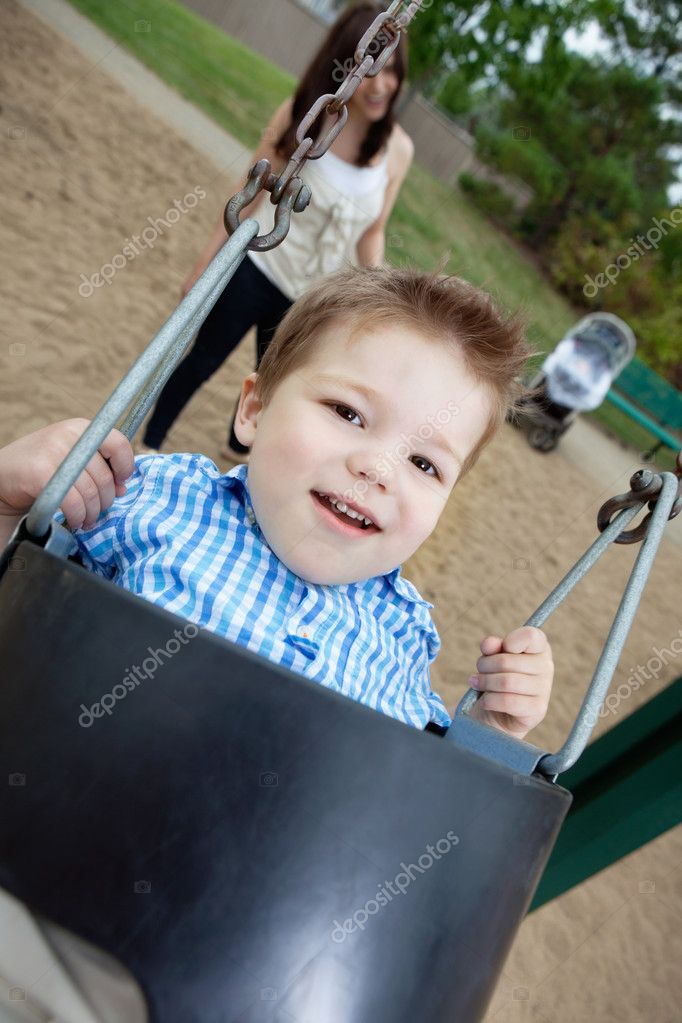 Close-up portrait of small boy swinging while mother standing in background — Stock Photo #7677329