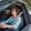 Smiling senior woman driving car - Stock Photo