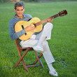 Man Playing Guitar Sitting in Lawn - Stockfoto