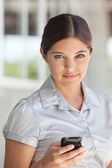 Attractive businesswoman holding cell phone — Stock Photo