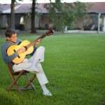 hombre tocando la guitarra en el césped — Foto de Stock