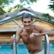 Smiling Middle Aged Man Standing in Pool - Stock Photo