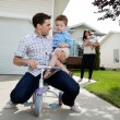 Stock Photo: Playful Father Sitting on Tricycle With Son