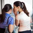 Female Whispering to Co-worker - Stock Photo