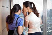 Female Whispering to Co-worker — Stock Photo