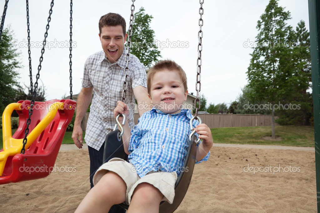 Happy father pushing boy on swing in playground — Stock Photo #7831846