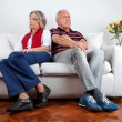 Couple Sitting on Sofa After Quarrel - Stock Photo