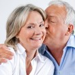 Woman Being Affectionately Kissed By Her Husband - Foto Stock