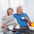 Senior Couple Reading Newspaper - Stock Photo