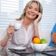 Woman Using Cell Phone at Breakfast Table — Stockfoto