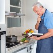 Senior Man Holding Recipe Book - Stock Photo