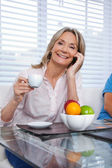 Woman Using Cell Phone at Breakfast Table — Stock Photo